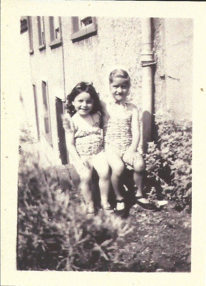 Gillian Blake and Shirley Squire sitting on the wall at 50 The Rock, Pilton in 1947